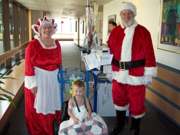 Jimmie Bass enjoys a visit from Mr. and Mrs. Clause in the hospital.