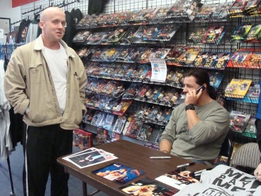 Independent Wrestler Michael Morbid waits while Al Snow calls Morbid's girlfriend, who wanted to attend the signing, but was unable to because of her work schedule.
