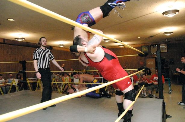 Maddog powers Ricky Kwong from the outside of the ring to the inside (Photo Credit: Mike Van Hoogstraat)
