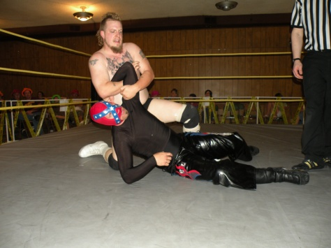 Eric Fantabulous works the arm of Rebel Lucha (Photo Credit: Brian Kelley)