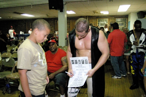 MMWA wrestlers took time to meet the fans during intermission. Blade takes time to autograph a poster for a young fan. (Photo credit: Mike Van Hoogstraat)