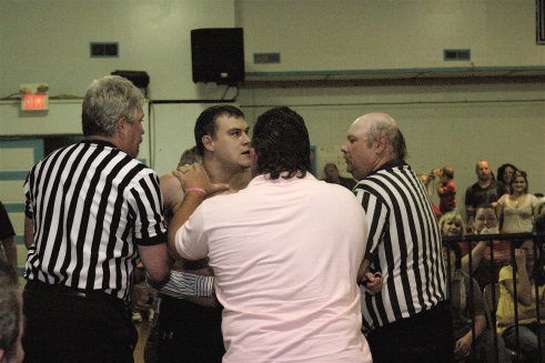 Dave Vaughn is restrained from attacking Kahyman. The match that the fans have been clamoring for, Vaughn vs. Kahyman is just around the corner. (Photo Credit by Mike Van Hoogstratt
