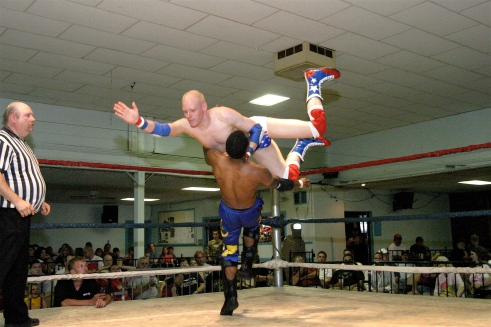 Johnny Courageous delivers a flying body press on the exciting young AJ Williams  (Photo Credit by Mike Van Hoogstratt)