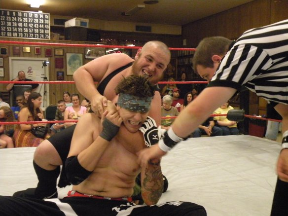 "One half of the LWA Champions at the time Evan Gelistico feels the viciousness of the Hooligans. (Photo credit Brian ""Flair"" Kelley)"