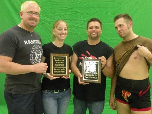 "A reunion between two warriors of the sport as Michael Strider and Jeremy Wyatt receive their 2008 MWR Match of the Year plaques. Pictured left to right Michael Strider, MWR Columnist Kari Williams, MWR Owner Brian Kelley, Jeremy ""The Belt Collector"" Wyatt."