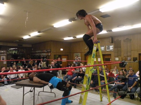 "A dive from the ladder onto the table from Aarons gains him another victory at IHW.(Photo Credit Brian ""Flair"" Kelley)"